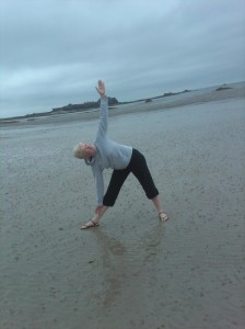Victoria doing triangle pose on the beach in Jersey.